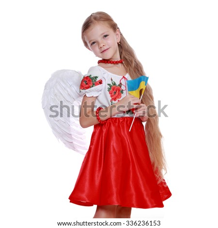 Studio image of emotional lovely little angel girl in a beautiful national Ukrainian suit holding a national flag isolated on a white background