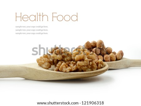 Studio image of fresh walnuts and hazelnuts on wooden spoons with soft shadows against a white surface. Copy space. - stock photo