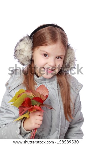 Studio image of lovely cheerful little girl in autumn clothes holding lots of colorful autumn leaves on white background