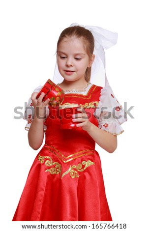 Studio image of lovely little girl holding wooden doll in tradition style Hohloma (a brand of Russian traditional ornaments used for painting on wooden things