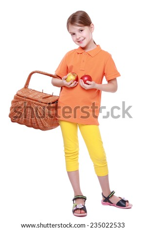 Studio image of lovely little girl holding yummy apples and picnic basket isolated over white background