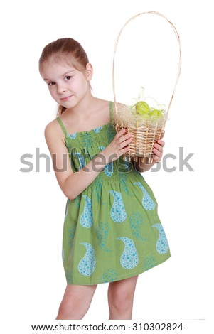 Studio image of lovely smiling little girl in a green dress is holding Easter basket with colored eggs isolated on white - stock photo