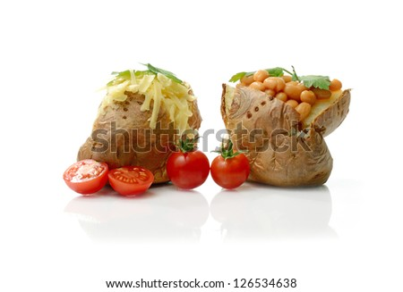 Studio image of two baked potatoes with grated cheese and baked beans with garnish. Copy space. - stock photo