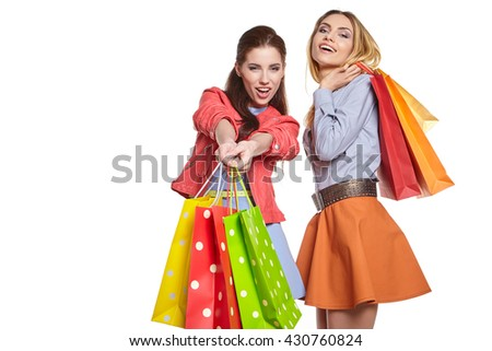 studio image of two beautiful young women, holding a few shopping bags, smiling and looking happy - stock photo