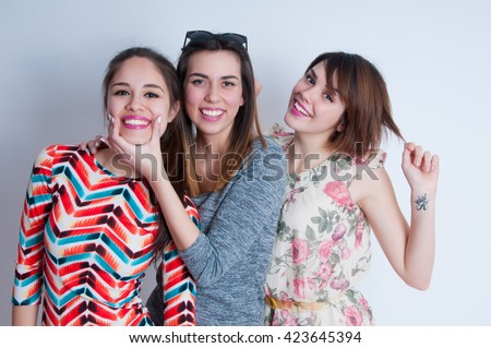 Studio lifestyle portrait of three best friends hipster girls wearing stylish bright dresses, going crazy and having great time together - stock photo