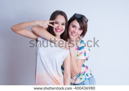 Studio lifestyle portrait of two best friends hipster girls wearing stylish bright outfits, t-shirts, denim shorts and glasses, going crazy and having great time together - stock photo