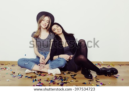 Studio lifestyle portrait of two best friends hipster girls wearing stylish outfits, going crazy and having great time together