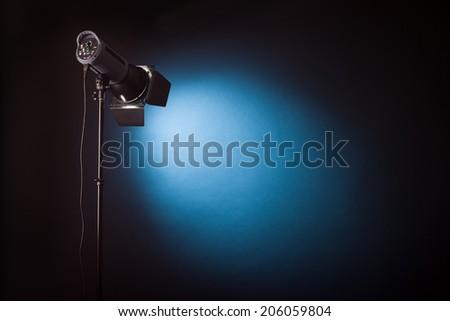 Studio light shines on dark background - stock photo
