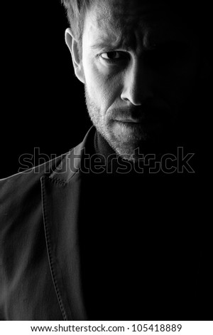 Studio low key portrait in black and white of a mid age man wearing a blazer.