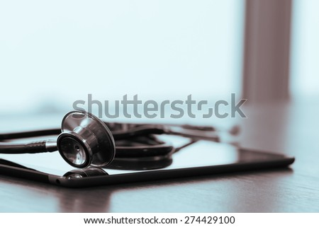 Studio macro of a stethoscope and digital tablet with shallow DOF evenly matched abstract on wood table background copy space - stock photo