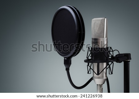 Studio microphone and pop shield on mic stand against gray background - stock photo