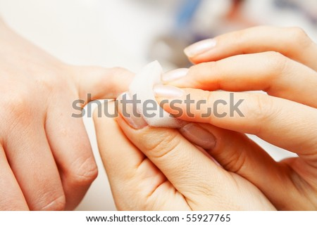 Studio nail - beautician polishing nails - stock photo