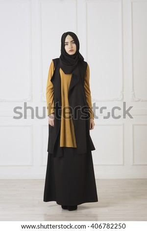 studio photo in full growth beautiful girl looks in the eastern Muslim dress and black scarf on head - stock photo