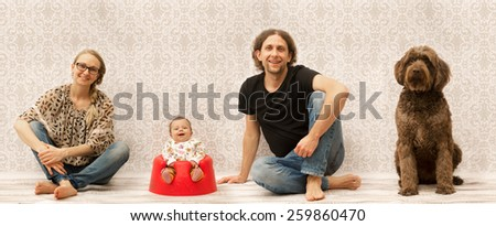 Studio photo of a happy family sitting next to each other - stock photo