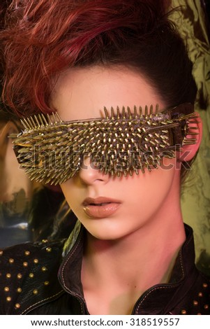 Studio photo of a young girl with red hair wearing glasses with gold spikes in the style of fashion and rock, on a shimmering background