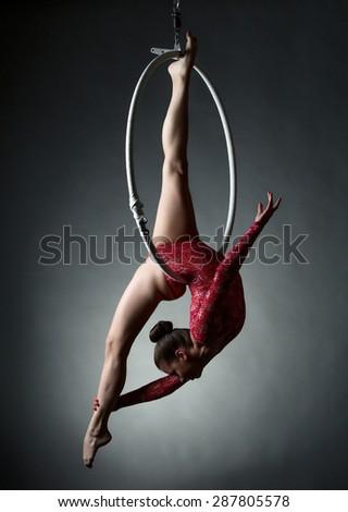 Studio photo of acrobatic girl dancing with hoop - stock photo