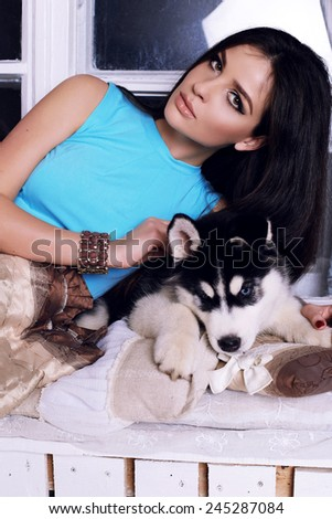 Studio photo of beautiful sexy brunette women with long straight hair wearing in blue top relaxing at home,sitting near the window and holding a cute little dogs of Husky - stock photo