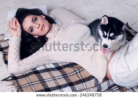 Studio photo of beautiful sexy brunette women with long straight hair wearing in cream sweater relaxing at home, lying on the wood floor and blanket with a cute little dog of Husky - stock photo