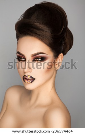 Studio photo of beauty young adult girl with creative make up and hairstyle in studio on grey background