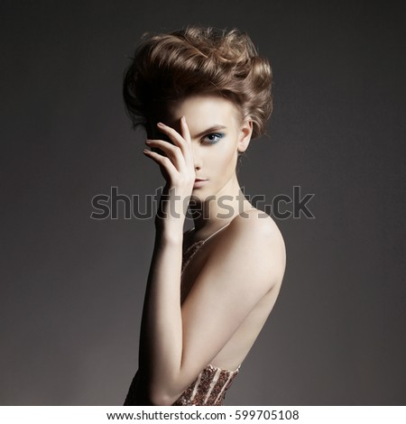 Studio photo of elegant lady with color smoky eyes makeup. Young woman with fashionable haircut
