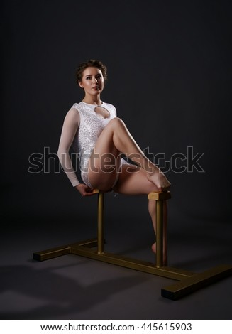 Studio photo of gymnast training on circus stands