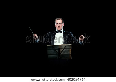 Studio photo of music conductor holding his baton - stock photo