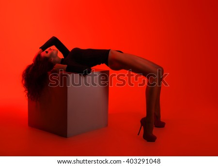 Studio photo of sexy woman in black lingerie against red background