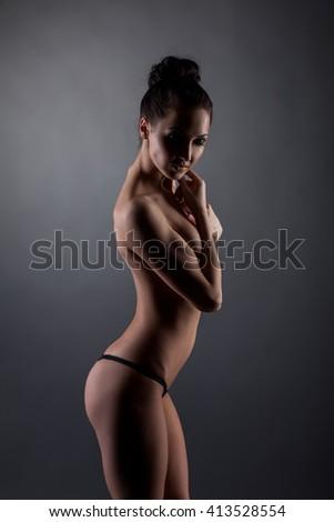 Studio photo of skinny girl in black thong panties - stock photo