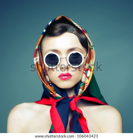 Studio photo of the girl in sunglasses and a scarf fun