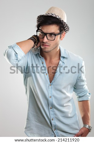 Studio photo of young attractive man wearing black glasses and hat - stock photo