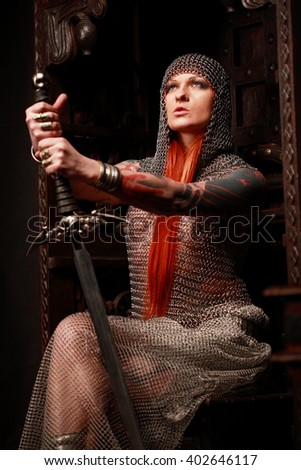 Studio photo session of attractive young redhead girl in chained armour sitting on the throne. Public photo studio interiors and studio equipment were used for this session