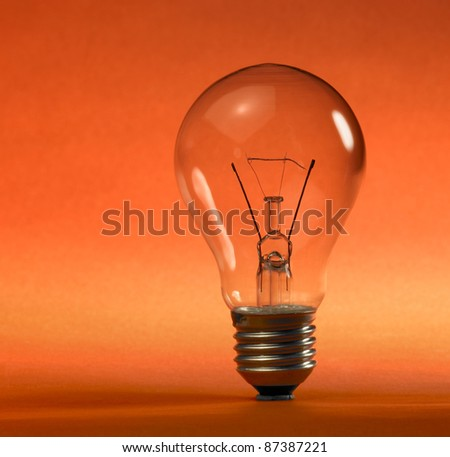 studio photography of a upright clear electric bulb in orange and red back - stock photo