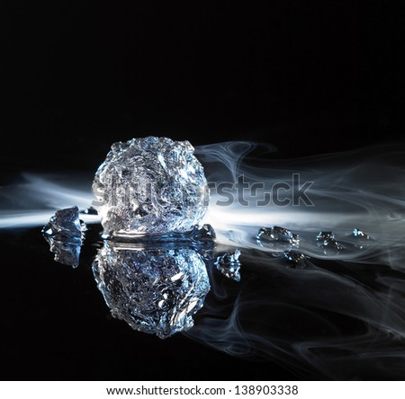 studio photography of ice crystals and smoke in black reflective back
