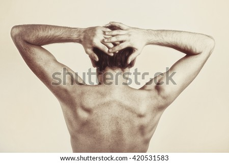 Studio photography of naked back of young man on white background