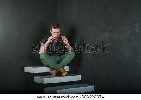 studio photography young brutal guy. man in sunglasses, T-shirt, jeans and high boots on background of black wall on white steps. sitting on the steps, took off his glasses and holds them in his hand