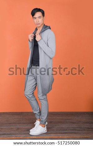 Studio picture of a full young handsome man in long stylish coat-orange background
