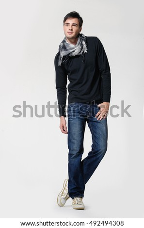 Studio picture of a young and handsome man in jeans with scarf posing