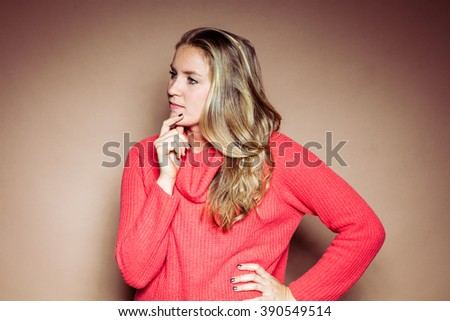 Studio portrait in front of beige background of blonde woman - stock photo