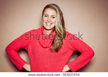 Studio portrait in front of beige background of blonde woman smiling - stock photo