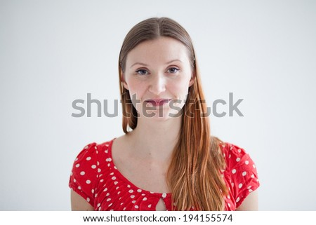Studio portrait in landscape orientation of happy smiling attractive woman wearing spotty red blouse - stock photo