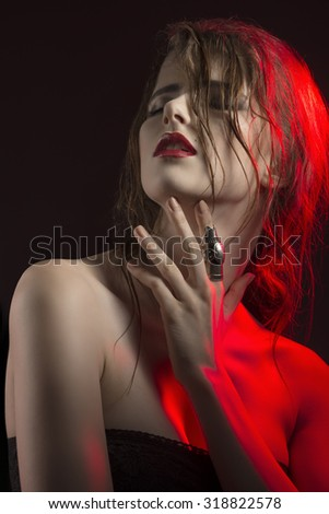 studio portrait in red half-light of sensual woman with wet hair, luxurious lips and cute ring  - stock photo
