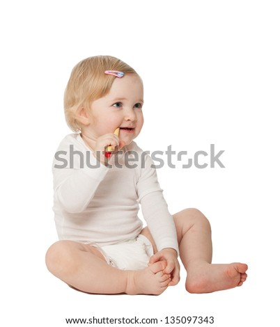 Studio portrait of a baby girl cleaning her teeth;  isolated on white