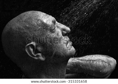 studio portrait of a bald old man showering - stock photo