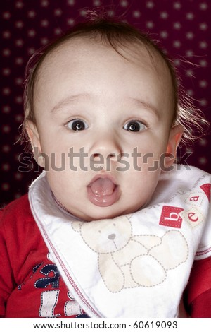 Studio portrait of a beautiful baby boy with a very funny facial expression. He's in front of a pink background with star patterns. He's wearing a red top and also wearing a bib. - stock photo