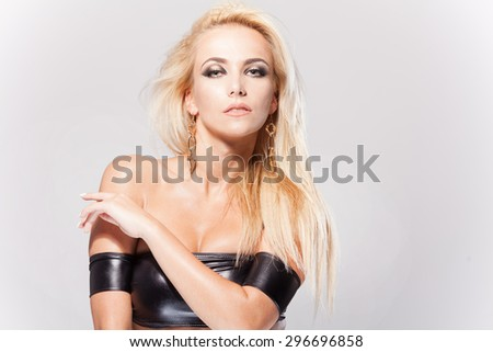 Studio portrait of a beautiful blonde with makeup and jewelry isolated on white - stock photo