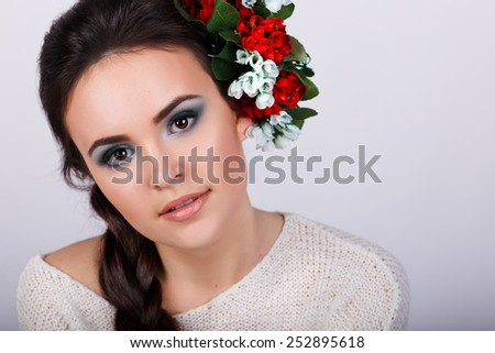 Studio portrait of a beautiful brunette with red flowers in her hair.girl with brown eyes  and glossy red lips wearing plaits against a grey background - stock photo