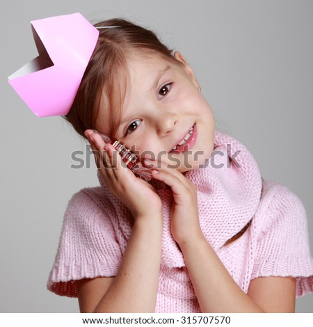 Studio portrait of a beautiful Caucasian girl with a charming smile in a knitted dress with a pink crown holding a gift on a gray background/Beauty little princess with pink tiara - stock photo