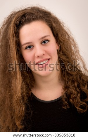 Studio portrait of a beautiful ginger teenage girl with long curly hair in black clothes isolated against a light grey background.