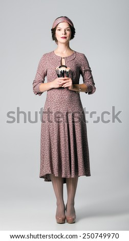 Studio portrait of a beautiful makeup artist with brushes in hands - stock photo