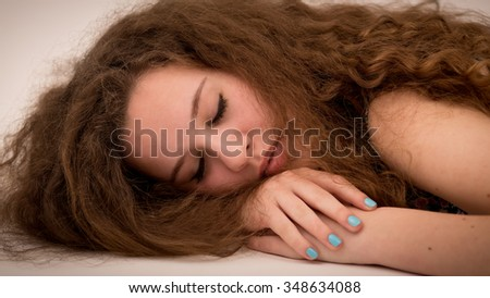 Studio portrait of a beautiful teenage ginger girl with long thick curly hair laying on the floor and nails painted blue with nail polish.